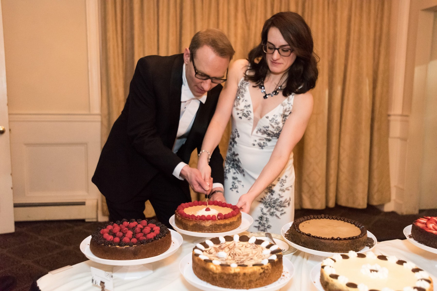Cutting into one of the ten cheesecakes we baked for our wedding!
